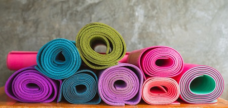 Photo of different coloured rolled yoga mats